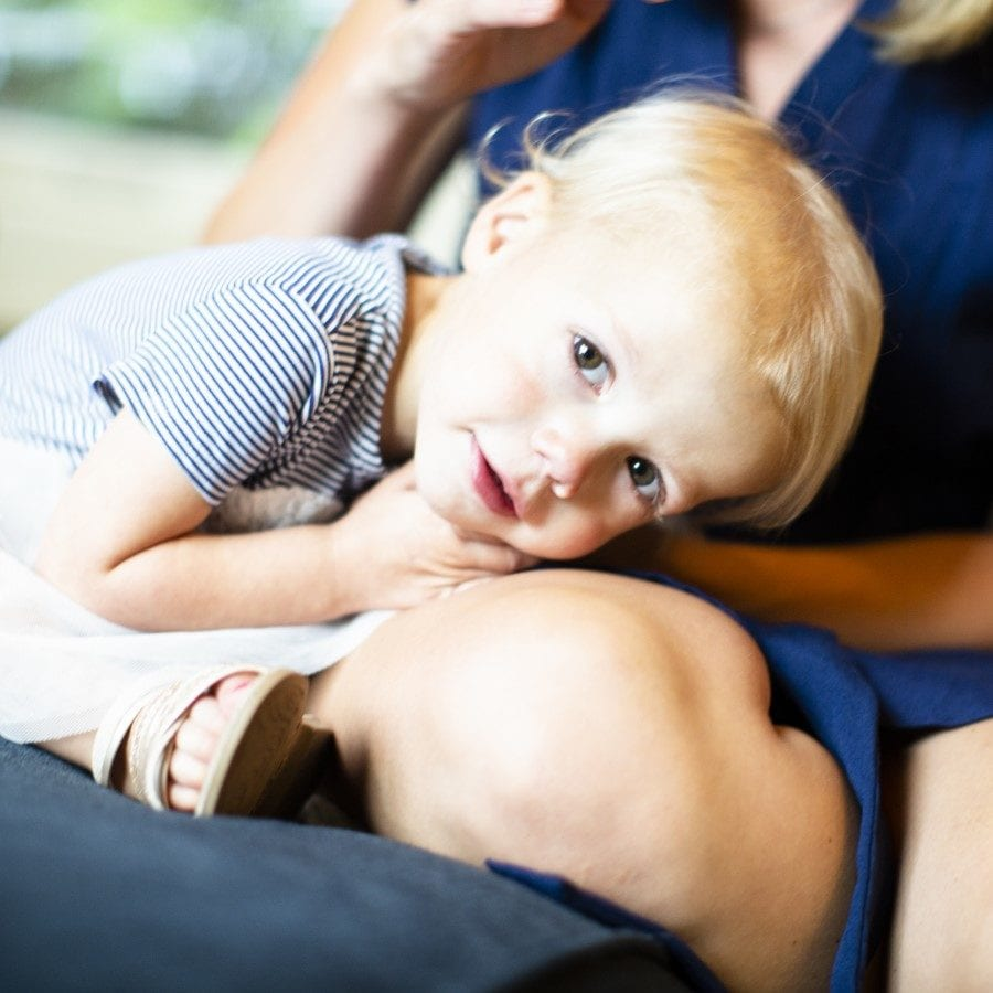 Young blond girl rests her head on her mother's knee and looks at the camera.