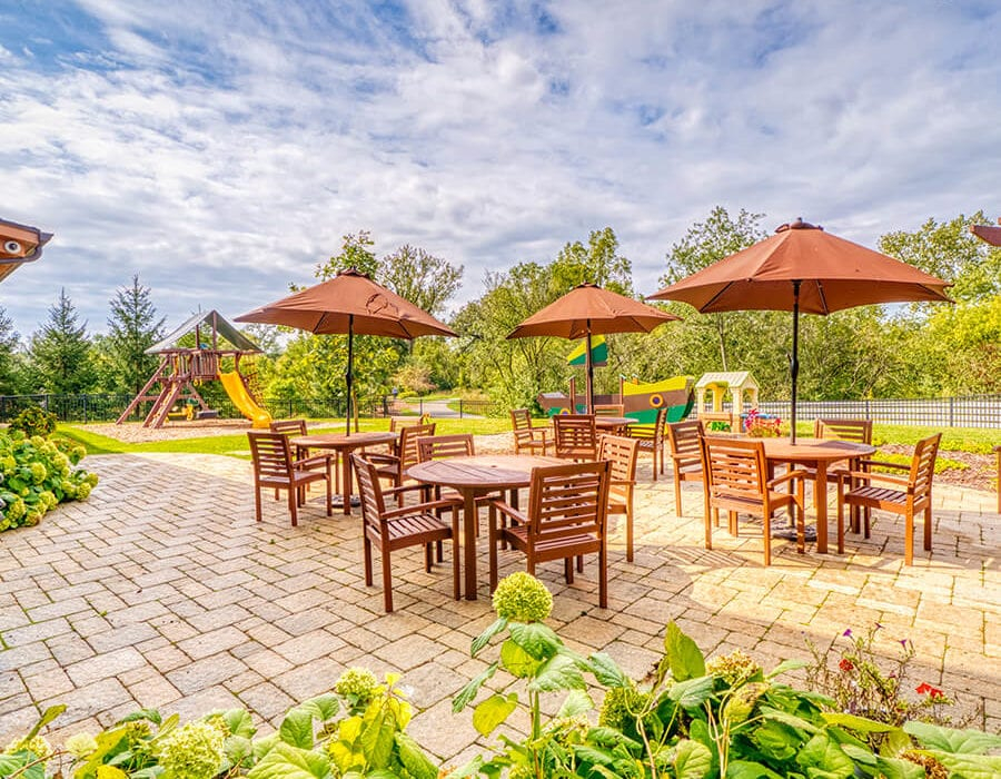 Outdoor patio with several wooden dining tables, chairs, and umbrellas.