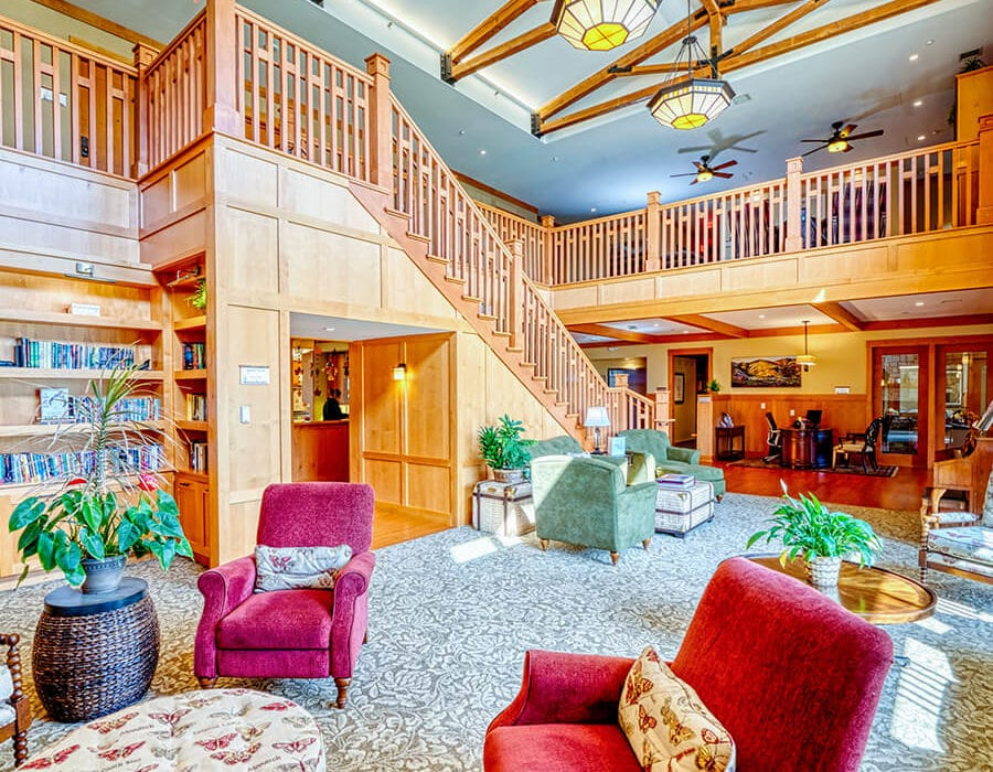 Expansive living room with tall staircase and several comfortable sofas and chairs.