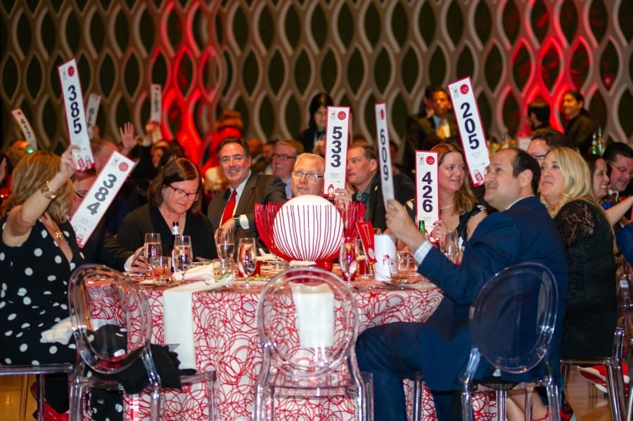 A group of people in evening clothes sit around a table and hold up auction paddles.